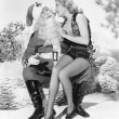 Woman and Santa Claus sitting together laughing — Stock Photo #12297076