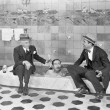 Two men sitting at the edge of a bathtub in suits and scrubbing a friends back — Photo