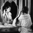 Woman fixing her long hair at her vanity table - Foto Stock