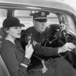 Woman sitting next to a policeman in his car holding a microphone in her hand — Foto Stock