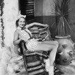 Young woman in a sun suit sitting on a chair — Lizenzfreies Foto