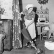 Woman doing housework with a vacuum cleaner — Stockfoto