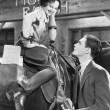 Woman sitting on a horse talking and flirting with a young man — Stock Photo