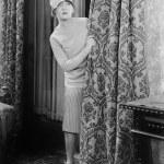 mujer joven mirando sorprendido detrás de una cortina — Foto de Stock