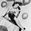 Young woman sitting on a table with balloons and sign - 图库照片