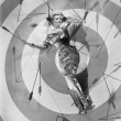 Stock Photo: Target of desire, young womlying on bulls eye with arrows around her