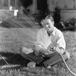 Stock Photo: Man watering the grass and reading