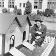 Man crouching next to duck house — Stok fotoğraf