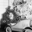 Little boy at Christmas sitting in his toy car — Zdjęcie stockowe