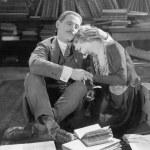 coppia seduta sul pavimento di una libreria tenendosi — Foto Stock