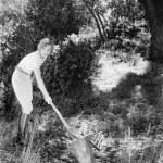 ung kvinna i en trädgård som gör trädgårdsarbete — Stockfoto