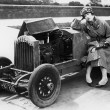 Young woman sitting next to small car looking at the engine in disbelieve — ストック写真