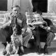Two men playing two harmonicas with an English Setter — Stockfoto