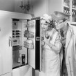 Man and woman standing in front of a refrigerator — Foto de Stock