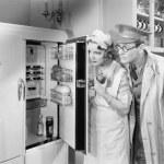 man en vrouw staande aan de voorkant van een koelkast — Stockfoto