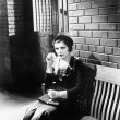 Young woman sitting n a bench in front of a jail cell — Stock fotografie