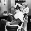 Stock Photo: Wombarber cutting man's hair