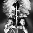 Two children sitting under a wreath holding a Christmas story book — Stock Photo #12298675