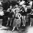Group of children performing with instruments and one girl dancing the hula - Stock Photo