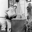 Young woman putting garbage into a garbage can — Stockfoto