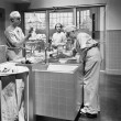 Two surgeons and a nurse in the scrub room preparing for an operation - Stock Photo