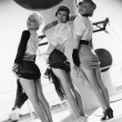 Three women looking over their shoulders and showing their legs — Stock Photo