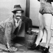 Man cleaning the floor looking at the legs of a woman - Foto de Stock