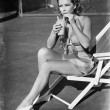 Young woman sitting on sling chair, sipping a drink — Photo