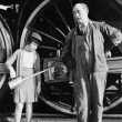 Little girl with an oil can standing next to a locomotive and the engine driver — Stok fotoğraf