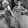 Two women playing a game of potato sack racing — Foto Stock
