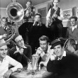 Group of men sitting in a diner with musicians behind them — Stock Photo