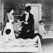 A woman with her nanny and two children in a bedroom talking with each other - Stock Photo
