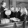 Teacher in a classroom with three pupils pointing to a globe — Stock Photo