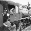 Stock Photo: Three men waiting at a steam locomotive