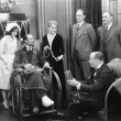 Stock Photo: Man in a wheel chair with a broken foot and a group of