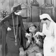 Young man with an eye patch being consoled by a nurse and a religious woman — ストック写真