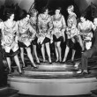 Chorus line of women showing off their legs to two men — Stock Photo #12299675