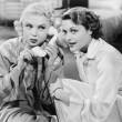 Two women sitting together and listening on the telephone receiver - Stock Photo