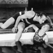 Man bending over to kiss a woman in a swimming pool — Foto Stock