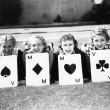 Four women are well suited to lay on the grass with playing cards in front of them - Stock Photo