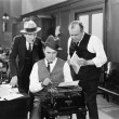 Three men in office hunched over typewriter — Foto Stock #12299871