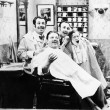 Foto Stock: Group of four men at barber shop singing