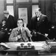 Foto Stock: Men at an office one on the telephone