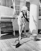 Female sailor swabbing boat deck — Stock Photo