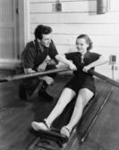 Man with woman using rowing machine — Stock Photo