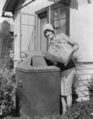 Portrait of woman taking out trash — Stock Photo