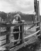 Mujer apoyándose en la valla de madera en rancho — Foto de Stock