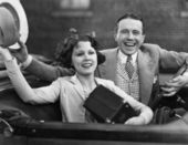 Portrait of happy couple waving in car — Stock Photo