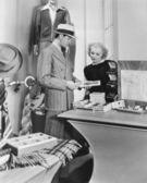Woman assisting male customer — Stock Photo