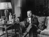 Přemýšlivý muž s drinkem na gauči — Stock fotografie